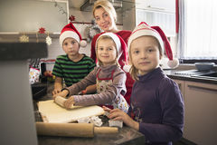 Kids making Christmas cookies with their mum. Stock Photos