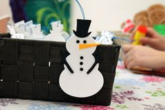 Kids Making Christmas Craft Ornaments. Kids making Christmas snowmen and gingerbread men ornaments crafts for gifts royalty free stock image