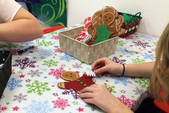 Kids Making Christmas Craft Ornaments. Kids making Christmas snowmen and gingerbread men ornaments crafts for gifts stock images