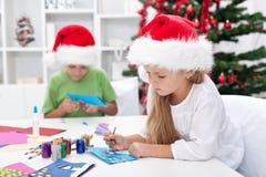 Kids making christmas greeting cards royalty free stock photos