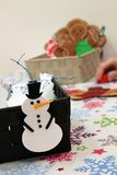 Kids Making Christmas Craft Ornaments. Kids making Christmas snowmen and gingerbread men ornaments crafts for gifts stock photos