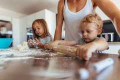 Kids making cookies with mother in kitchen. Little boy with his mother and sister preparing dough with rolling pin on kitchen table. Mother with kids cooking Stock Photo