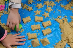 Kids making different shapes by sand with mould. S Stock Images