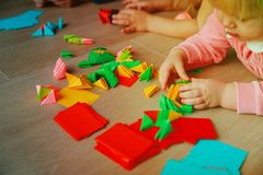 Kids making origami crafts with paper. Learning activities stock photography