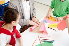 Kids making paper airplanes. Children making paper airplanes with colored paper during art lesson while sitting at classroom desk with teacher royalty free stock photos