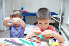 Kids making paper colored garland, siblings craft, brother and s Stock Image