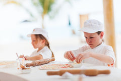 Kids making pizza. Adorable little girl and cute boy dressed as chefs making pizza stock photos