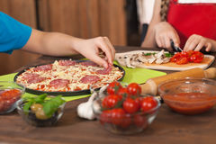 Kids making a pizza at home Royalty Free Stock Images
