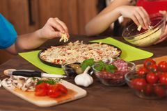 Kids making a pizza at home - putting the grated cheese on. Closeup on hands, shallow depth Royalty Free Stock Photos