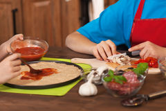 Kids making a pizza at home - spreading the pizza sauce Stock Images