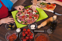 Kids making a pizza - placing the ingredients on the doug Royalty Free Stock Images