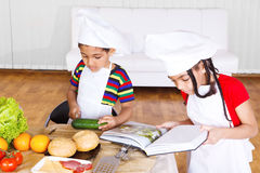 Kids making salad. Kids reading cook book and making salad Stock Photos