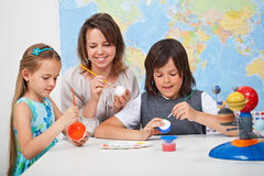 Kids making a scale model of the solar system in science class-. Kids making a scale model of the solar system in science class - helped by their teacher stock image