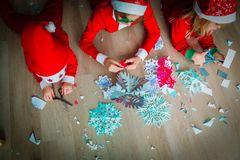 Kids making snowflakes from paper, Christmas crafts. Prepare for family Christmas celebration royalty free stock photo