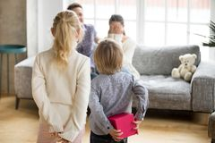 Kids making surprise to mommy on mothers day, rear view. Rear view at cute children son and daughter holding gift box behind back making surprise to mommy on Stock Images