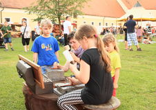 Kids making their own bracelet. Kids - concentrated girls making their own leather bracelet at 'Conquest of water castle Svihov' (Czech Republic, the 1st of July Royalty Free Stock Photos