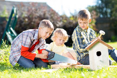 Kids making together nesting box outdoors in summer. Older boy teaches his younger brother handicrafts. Kids making together nesting box outdoors. Older boy Royalty Free Stock Photos