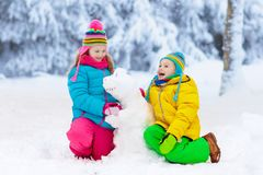 Kids making winter snowman. Children play in snow. Kids making snowman in snowy winter park. Children play in snow. Boy and girl in colorful jackets and hats stock photos