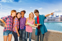 Kids with map standing together on embankment Stock Photography