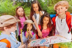 Kids with map on treasure hunt navigation activity. Group of kids in forest examine and point with finger on map during treasure hunting hike activity in summer royalty free stock images