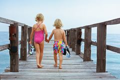 Kids with masks, fins going to snorkel in tropical sea royalty free stock photos