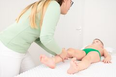 Kids massage concept background. Young female massage therapist giving a 6 year old boy leg massage. Physical therapy.