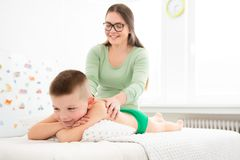 Kids massage concept background. Young female massage therapist giving a 6 year old boy back massage. Physical therapy.