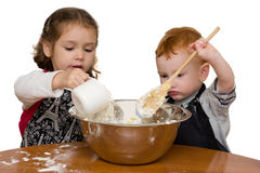 Kids measuring and mixing in kitchen. Two kids measuring and mixing into large mixing bowl. Isolated on white stock photo