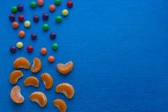 Kids menu, candies and mandarins on blue background. Kids menu, colorfu  candies and mandarins on blue background Royalty Free Stock Photos