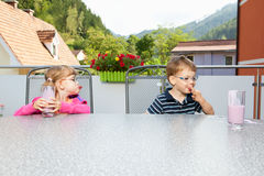 Kids with milkshake. Children, mishap and malicious joy Stock Photos