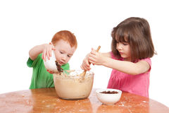 Kids mixing and pouring cake ingredients. Boy pouring chocolate chips into cake mix girl is stirring. Isolated on white stock image