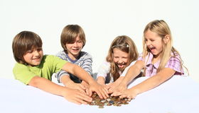 Kids with money. Four happy kids - two girls and two boys dividing money - savings of czech crowns - small change Stock Photography