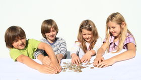 Kids with money. Four happy kids - two girls and two boys dividing money - savings of czech crowns - small change Stock Image