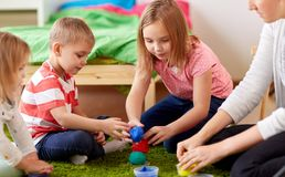 Kids and mother with modelling clay or slimes. Childhood, leisure and people concept - group of happy kids and and mother with modelling clay or slimes at home Stock Image