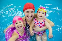 Kids with mother in pool Stock Image