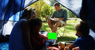 Kids and mother using tablet while father looking at the map 4k. Kids and mother using tablet while father looking at the map at campsite 4k stock video