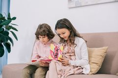 Kids with mothers day greeting cards sitting on couch. At home stock photo