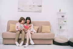 Kids with mothers day greeting cards sitting. On couch royalty free stock photos