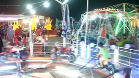 Kids on motorbike ride in amusement park stock footage