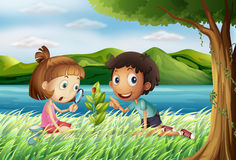 Kids near the river with a magnifying glass Stock Photo