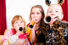 Kids with noisemakers making noise on party. Looking into the camera Stock Image