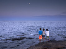 Kids by the ocean. 3 kids looking at the moon by the ocean Royalty Free Stock Photography