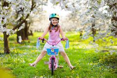 Free Kids On Bike In Spring Park. Girl Riding Bicycle Stock Photo - 215561250