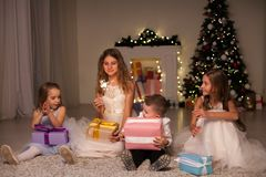 Kids open Christmas presents new year holiday lights sparklers. Kids open Christmas presents new year holiday lights royalty free stock photo