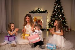 Kids open Christmas presents new year holiday lights sparklers. Kids open Christmas presents new year holiday lights stock image