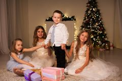 Kids open Christmas presents new year holiday lights sparklers. Kids open Christmas presents new year holiday lights royalty free stock images