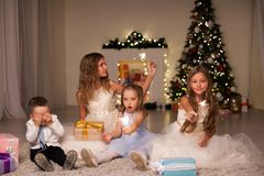 Kids open Christmas presents new year holiday lights sparklers. Kids open Christmas presents new year holiday lights royalty free stock image