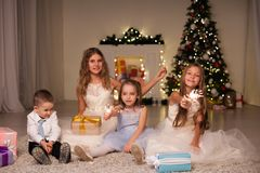 Kids open Christmas presents new year holiday lights sparklers. Kids open Christmas presents new year holiday lights royalty free stock photos