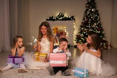 Kids open Christmas sparklers gift new year holiday lights Christmas tree garlands. Kids open Christmas sparklers gift new year holiday lights Christmas tree royalty free stock image