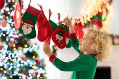 Kids opening Christmas presents. Child searching for candy and gifts in advent calendar on winter morning. Decorated Christmas. Tree for family with children stock photo
